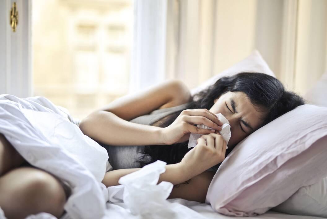 Bolesna žena leži u krevetu i briše nos