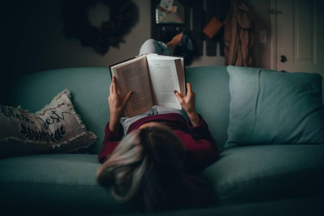 Djevojka čita knjigu i leži na trosjedu