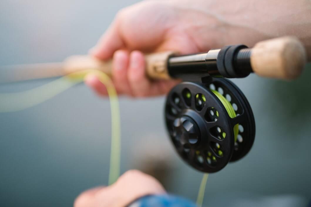 Ribolovac u ruci drži ribički štap i lovi ribe